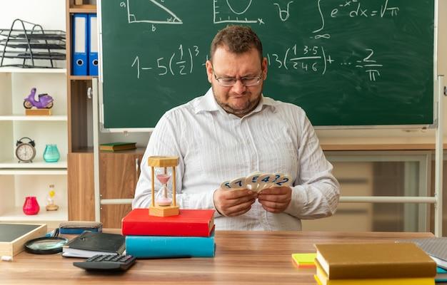 Zdezorientowany młody nauczyciel w okularach siedzi przy biurku z przyborami szkolnymi w klasie, trzymając i patrząc na fanów liczb