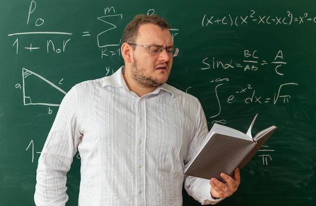 Zdezorientowany młody nauczyciel w okularach stojący przed tablicą w klasie czyta notatnik