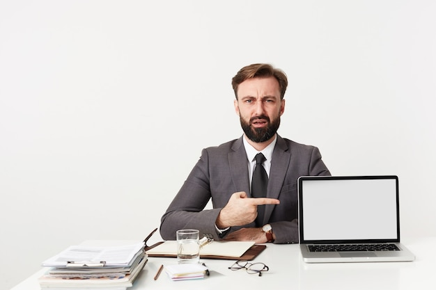 Zdezorientowany młody przystojny brunetka mężczyzna z brodą i krótką fryzurą pozuje na białej ścianie przy stole roboczym i pokazuje palcem wskazującym na swoim laptopie