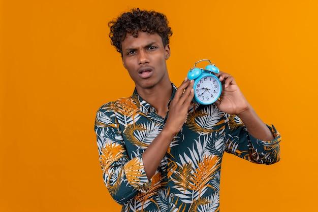Zdezorientowany młody przystojny ciemnoskóry mężczyzna z kręconymi włosami w koszulce z nadrukiem liści trzyma niebieski budzik i pokazuje czas