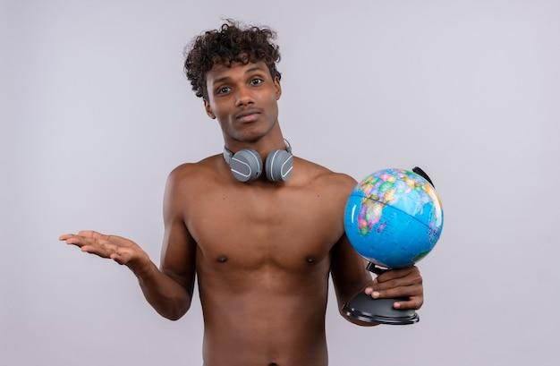 Zdezorientowany młody przystojny ciemnoskóry mężczyzna z kręconymi włosami w słuchawkach, trzymając kulę ziemską