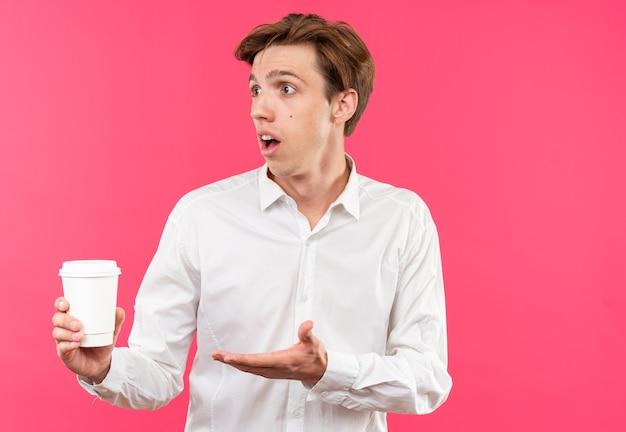 Zdezorientowany młody przystojny facet ubrany w białą koszulę, trzymający i wskazujący ręką przy filiżance kawy odizolowany na różowej ścianie