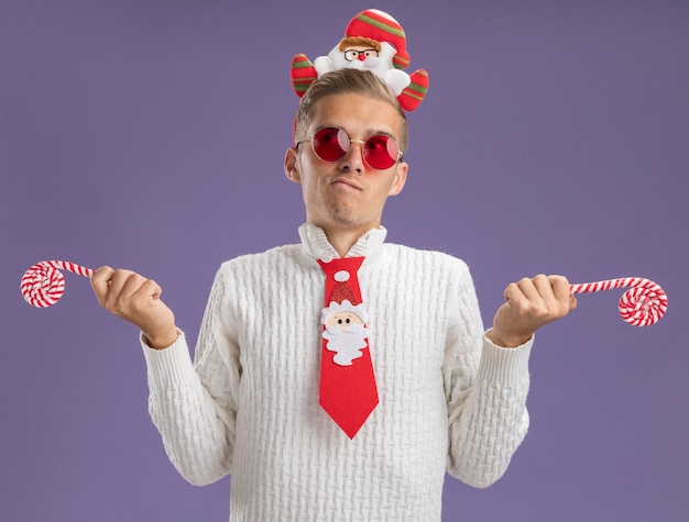 Zdezorientowany młody przystojny facet ubrany w opaskę świętego mikołaja i krawat w okularach, trzymając świąteczne cukierki laski, patrząc na bok na białym tle na fioletowym tle