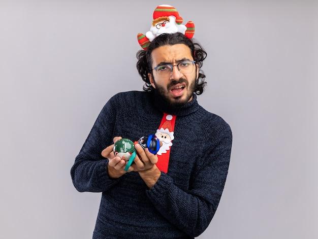 Zdezorientowany młody przystojny facet ubrany w świąteczny krawat z obręcz do włosów, trzymając bombki na białym tle