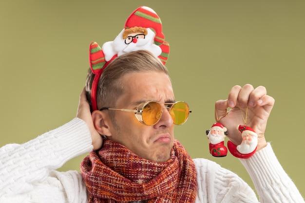 Zdezorientowany młody przystojny facet w opasce świętego mikołaja i szaliku trzyma i patrzy na świąteczne ozdoby świętego mikołaja kładąc rękę za głową odizolowaną na oliwkowej ścianie