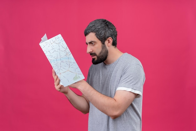 Zdezorientowany młody przystojny kaukaski podróżnik mężczyzna trzyma i patrząc na mapę na różowym tle z miejsca na kopię