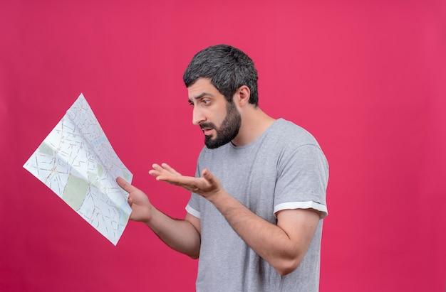 Zdezorientowany młody przystojny kaukaski podróżnik mężczyzna trzyma i patrzy na mapę i pokazuje pustą dłoń na różowym tle z miejsca na kopię