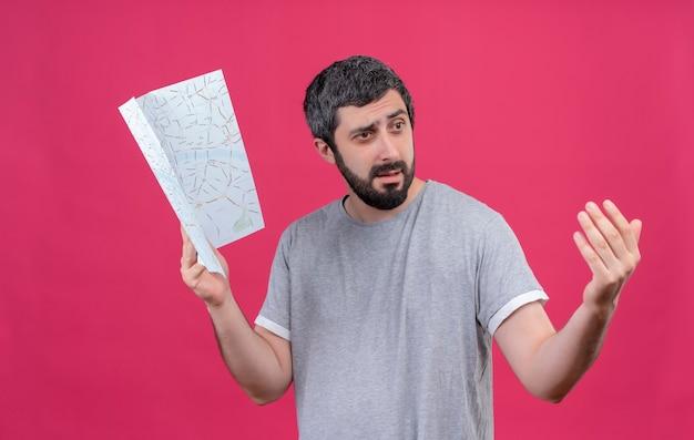 Zdezorientowany młody przystojny kaukaski podróżnik mężczyzna trzyma mapę patrząc z boku i robi gest chodź tutaj na różowym tle