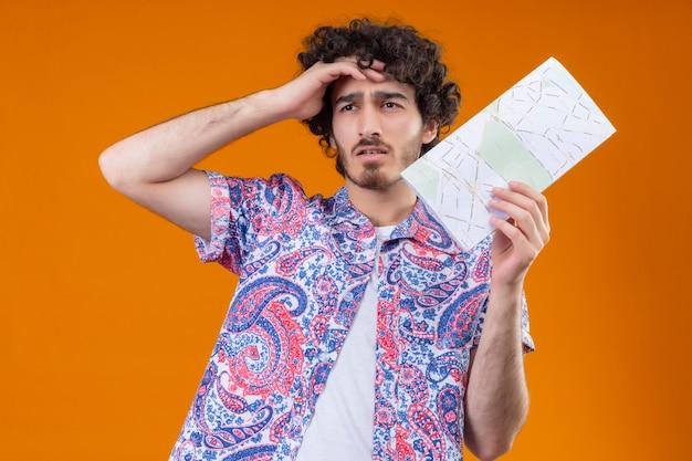 Zdezorientowany młody przystojny kręcone podróżnik mężczyzna trzyma mapę ręką na czole na odizolowanej pomarańczowej przestrzeni