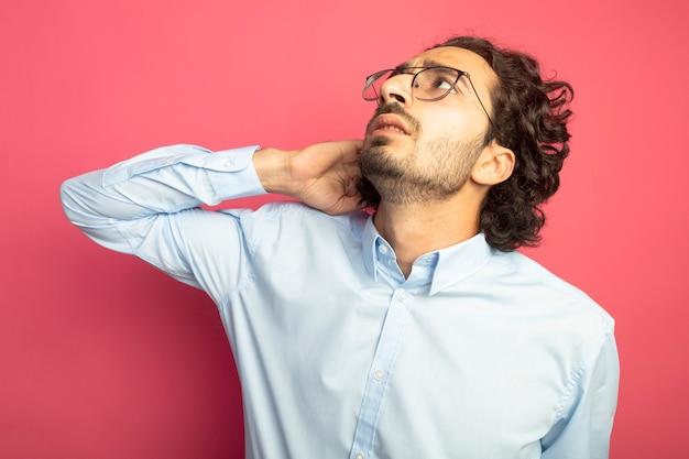 Zdezorientowany młody przystojny mężczyzna w okularach dotykając włosów patrząc w górę na białym tle na różowej ścianie