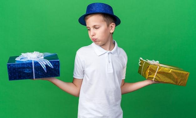 Zdezorientowany młody słowiański chłopak w niebieskiej imprezowej czapce, trzymający i patrzący na pudełka z prezentami na zielonej ścianie z miejscem na kopię