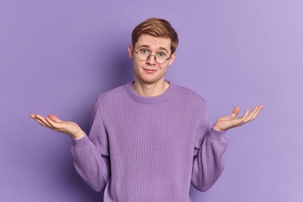 Zdezorientowany młodzieniec wzrusza ramionami rozpościera dłonie stoi niezdecydowany w domu ubrany w swobodny sweter nosi okrągłe okulary