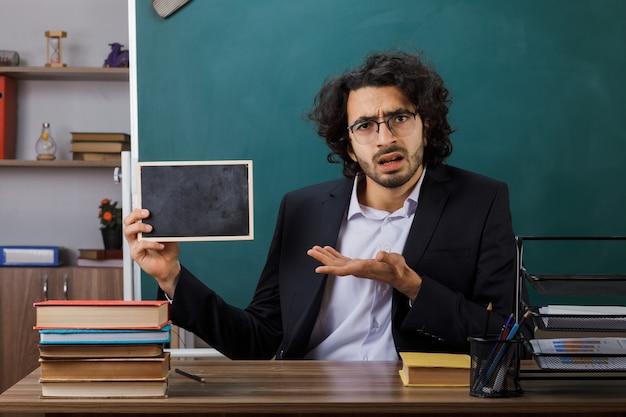 Zdezorientowany nauczyciel płci męskiej w okularach, trzymający i wskazujący ręką przy mini tablicy, siedzący przy stole z narzędziami szkolnymi w klasie