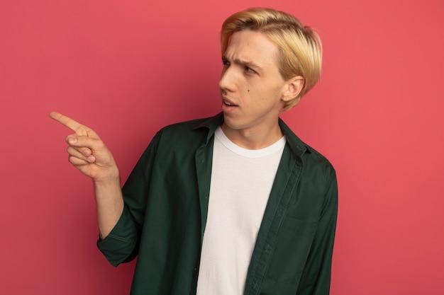 Zdezorientowany patrząc na bok młody blondyn ubrany w zielony t-shirt wskazuje na bok