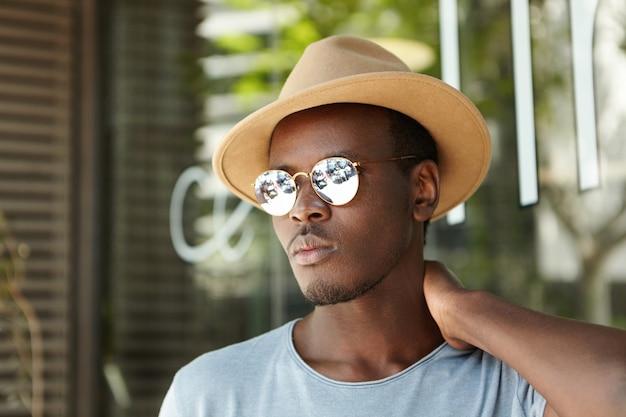 Zdezorientowany, poważny młody czarny mężczyzna ubrany w modne ciuchy pocierający szyję, zdziwiony i niezdecydowany, myśląc o czymś ważnym