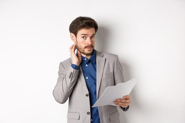 Zdezorientowany pracownik biurowy w garniturze drapie się po brodzie i nie ma pojęcia, nie rozumie dokumentu, trzyma papier z niezdecydowaną twarzą, białe tło.