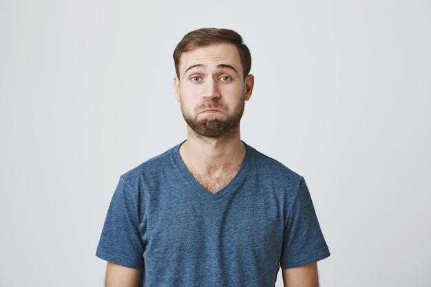 Zdezorientowany przystojny brodaty mężczyzna dąsa się