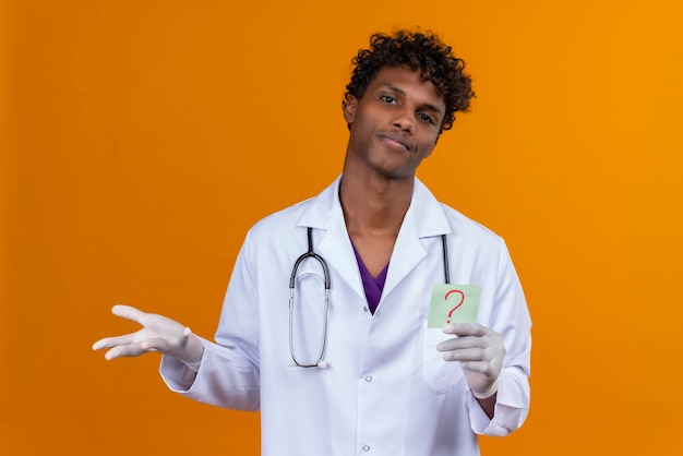 Zdezorientowany przystojny ciemnoskóry mężczyzna z kręconymi włosami w białym fartuchu ze stetoskopem pokazujący papierową kartę ze znakiem zapytania