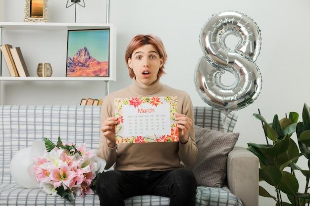 Zdezorientowany przystojny facet na szczęśliwy dzień kobiet trzymający kalendarz siedzący na kanapie w salonie