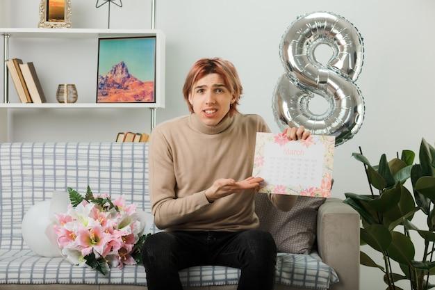 Zdezorientowany przystojny facet na szczęśliwy dzień kobiety trzymający i wskazujący ręką w kalendarzu, siedzący na kanapie w salonie