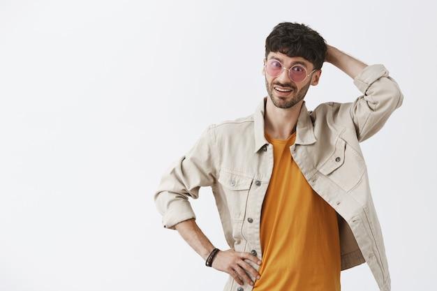 Zdezorientowany przystojny facet pozuje przy białej ścianie z okularami przeciwsłonecznymi