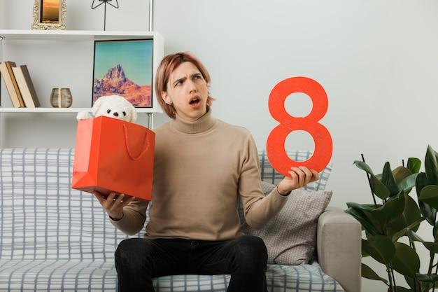 Zdezorientowany przystojny facet w szczęśliwy dzień kobiet trzymający numer osiem z torbą na prezenty siedzący na kanapie w salonie