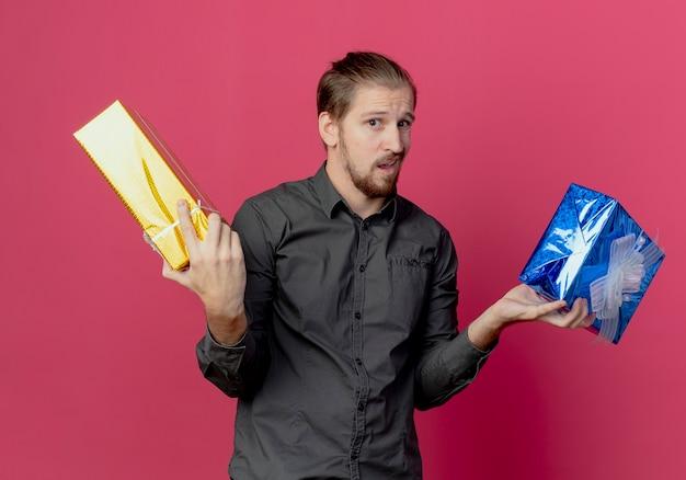 Zdezorientowany przystojny mężczyzna trzyma pudełka na prezent, patrząc na białym tle na różowej ścianie