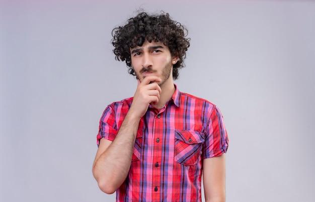 Zdezorientowany przystojny mężczyzna z kręconymi włosami, w koszuli w kratę, trzymający rękę na brodzie