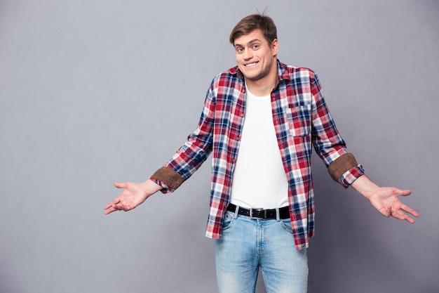 Zdezorientowany przystojny młody mężczyzna w kraciastej koszuli stoi i wzrusza ramionami