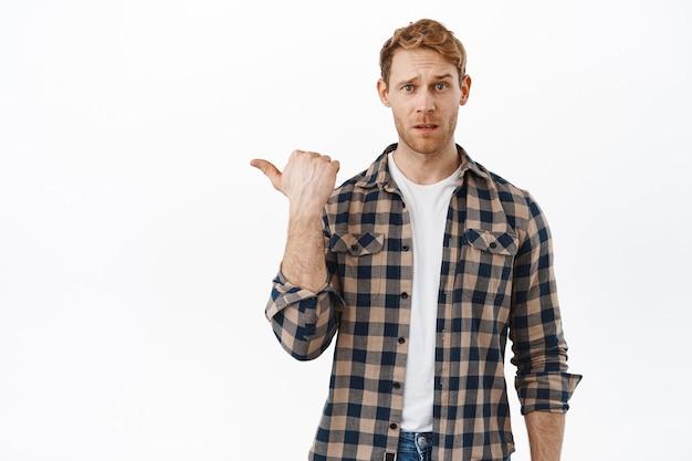 Zdezorientowany, rudowłosy dorosły mężczyzna wskazujący palcem na coś dziwnego, unoszący brwi i patrzący z powątpiewaniem, wahający się co do produktu, niepewny, stojący nad białą ścianą
