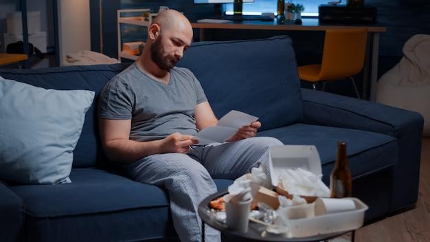 Zdezorientowany sfrustrowany zestresowany młody człowiek czytający list