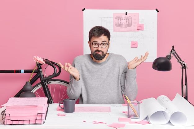Zdezorientowany student wzrusza ramionami, nie wie, jak zrobić zadanie domowe, twarze problematyczne w pracy, spojrzenia z niezdecydowanym wyrazem twarzy, otoczone projektami karteczki samoprzylepne z przypominającymi informacjami