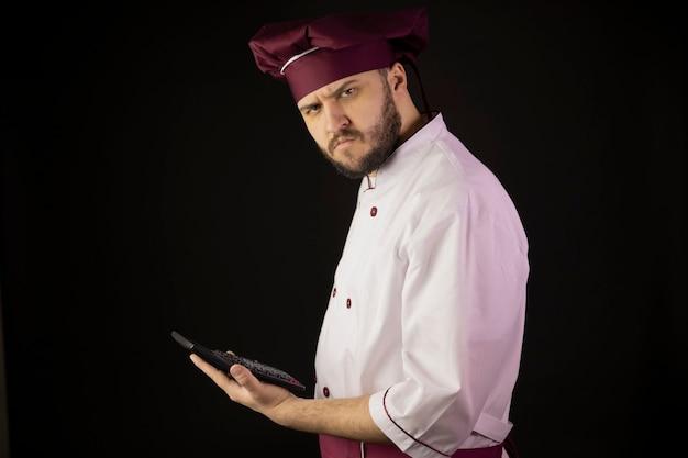 Zdezorientowany szef kuchni w mundurze podejrzliwie trzyma kalkulator