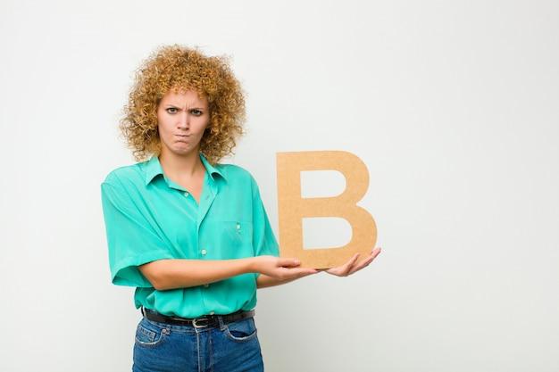 Zdezorientowany, wątpliwy, myślący, trzymając literę b alfabetu w celu utworzenia słowa lub zdania.