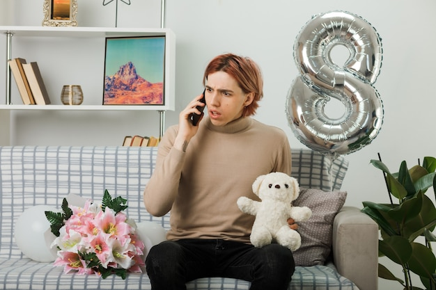Zdezorientowany, wyglądający na boku, przystojny facet na szczęśliwy dzień kobiet trzymający pluszowego misia, który rozmawia przez telefon, siedząc na kanapie w salonie