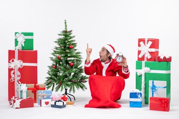 Zdezorientowany, zaskoczony młody człowiek świętuje nowy rok lub święta bożego narodzenia siedząc na ziemi i trzymając zegar w pobliżu prezentów i udekorowane choinkę na białym tle