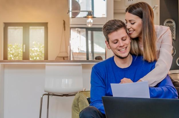 Zdj? cie weso? a kochaj? ca para m? odych przy u? yciu komputera przeno? nego i analizowanie ich finansów z dokumentami. spójrz na gazety.