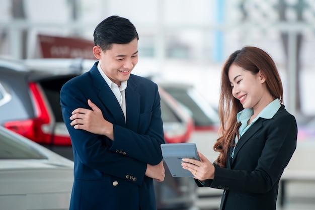 Zdjęcia azjatyckich klientów i szczęśliwych sprzedawców, którzy kupują nowe samochody, które zawierają umowy sprzedaży z dealerami samochodowymi u dealerów samochodowych.