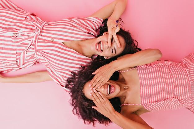 Zdjęcia dwóch młodych i rozmawiających dziewczyn w pięknej sukience i jasnej sukience w paski, uśmiechniętych i przymykających oczy