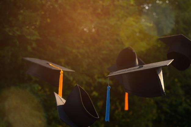 Zdjęcia kapeluszy absolwentów na tle są niewyraźne.