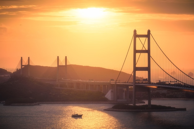 Zdjęcia lotnicze budynków miejskich, wzgórz i mostu nad rzeką o zachodzie słońca