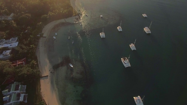 Zdjęcia lotnicze jachtów w pobliżu wybrzeża z domami z następującym widokiem na wyspę i ocean o złotym zachodzie słońca. wakacje na mauritiusie