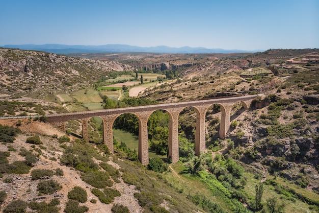 Zdjęcia lotnicze, kamienny most rozciąga się nad zieloną doliną w słońcu. zielona droga, teruel, hiszpania.