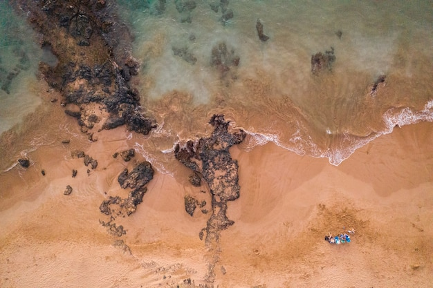 Zdjęcia lotnicze kobiety leżącej na brzegu plaży