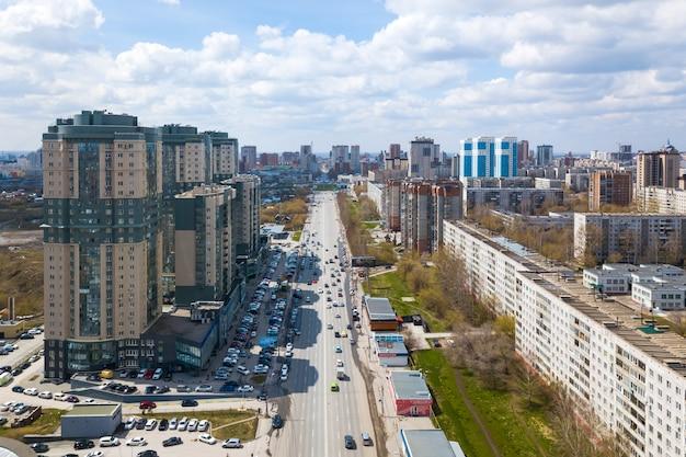 Zdjęcia lotnicze nowoczesnego miasta: wieżowce, duża droga, sklepy i parki w ciepły letni dzień z błękitnym niebem.