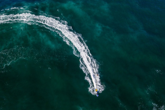 Zdjęcia lotnicze osoby na nartach wodnych w jasnozielonej wodzie morskiej
