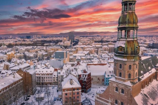 Zdjęcia lotnicze pięknego zachodu słońca nad zaśnieżonym miastem ryga z rzeką dźwiną i centrum miasta