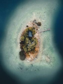 Zdjęcia lotnicze przedstawiające wyspę z drzewami i dom z drewnianym molo pośrodku niczego