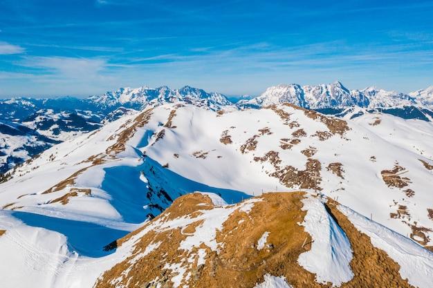 Zdjęcia lotnicze wysokich ośnieżonych gór w austrii w słoneczny dzień