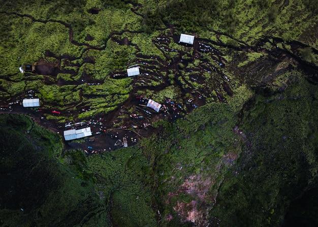 Zdjęcia lotnicze wzgórz pokrytych zielenią w otoczeniu budynków w nasłonecznionym miejscu